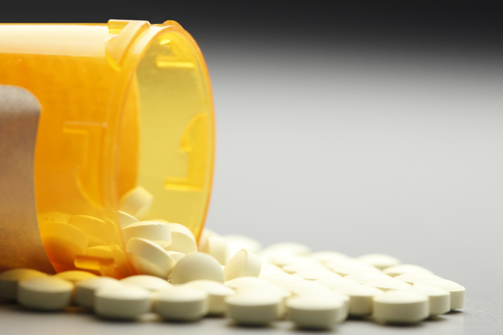 Pills spill out of a prescription pill bottle on a graduated gray background. The negative space created by the gray background provides ample room for text and copy.